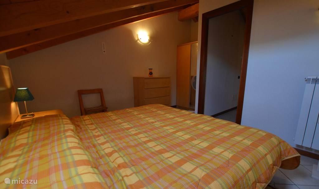 De grote slaapkamer met twee-persoonsbed en kledingkast.