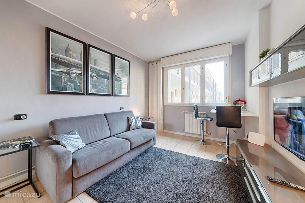 De moderne woonkamer met twee-persoons slaapbank, bartafel, TV meubel en kledingkast.