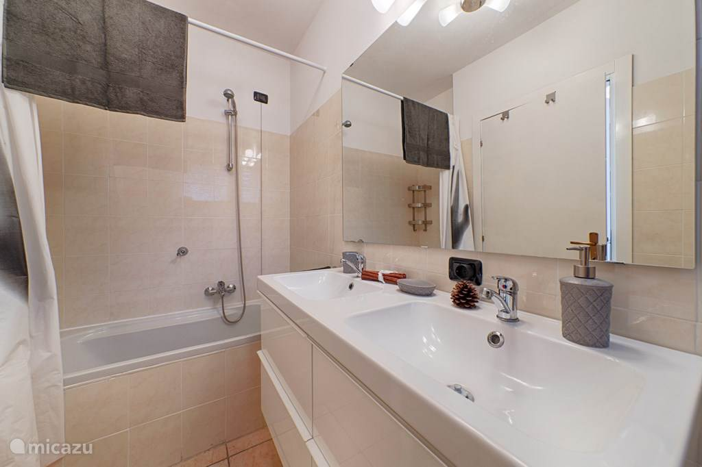 De stijlvolle badkamer met ligbad, wastafel, bidet en toilet.