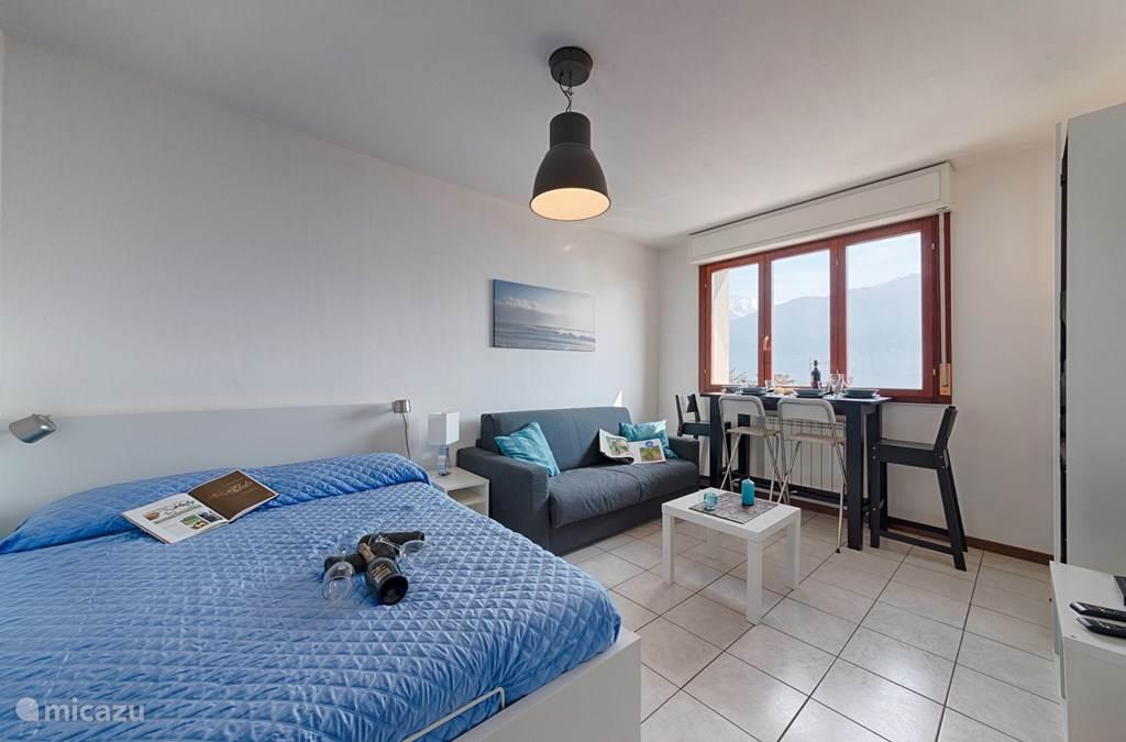 De woonkamer met het twee-persoonsbed en de twee-persoonsslaapbank.