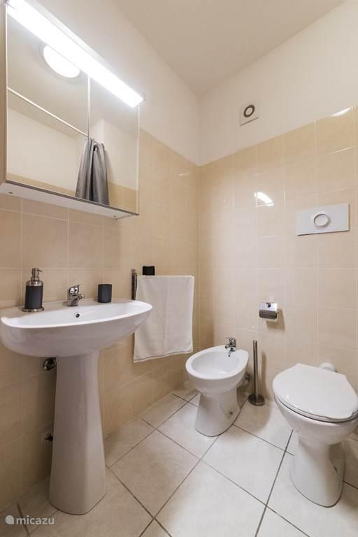 De badkamer met ligbad, wastafel, bidet en toilet.