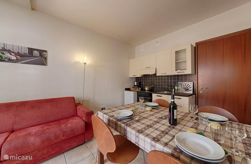 De woonkamer met twee-persoons slaapbank, de keuken en eettafel.