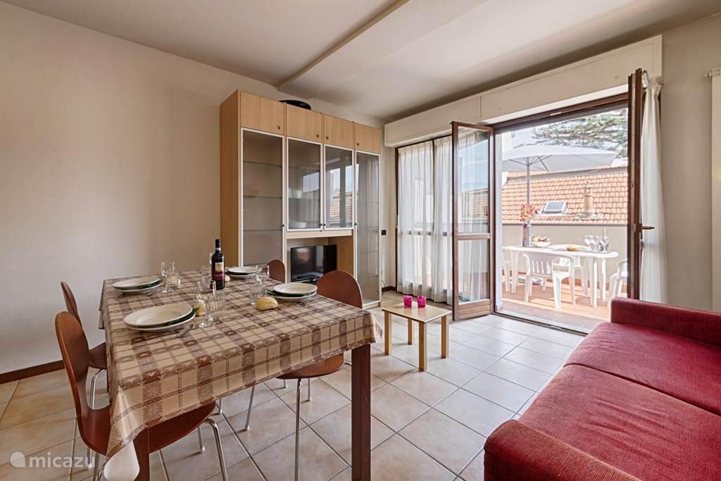 De woonkamer met de eettafel en de twee-persoonsslaapbank en het aangrenzende balkon.