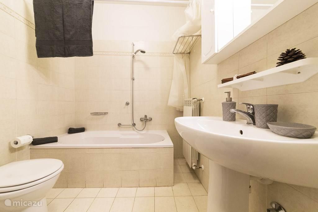 De badkamer met ligbad, wastafel bidet en toilet.