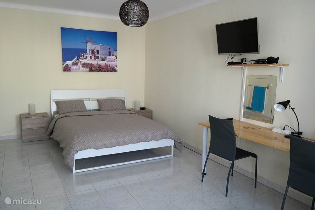slaapkamer met tv klerenkast bureau en heerlijk openschuif baren deuren