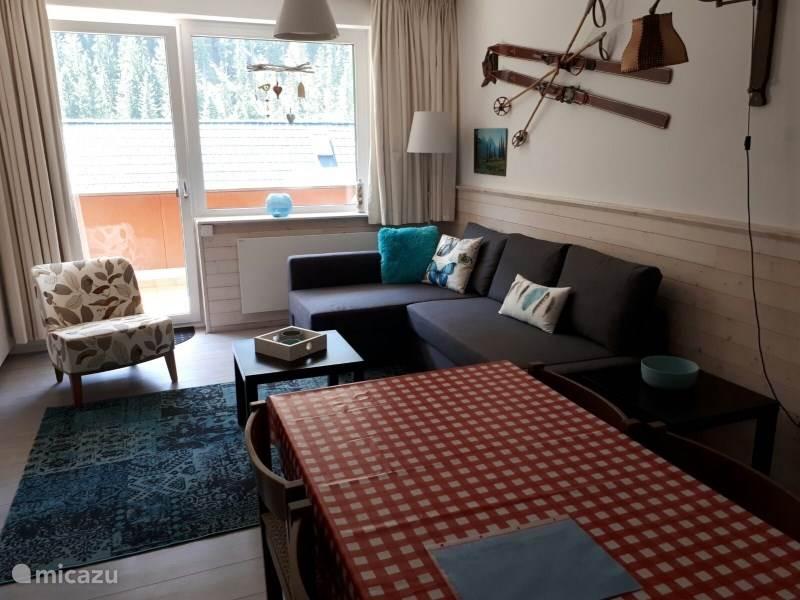 De woonkamer met laminaat en een 2-persoons slaapbank.