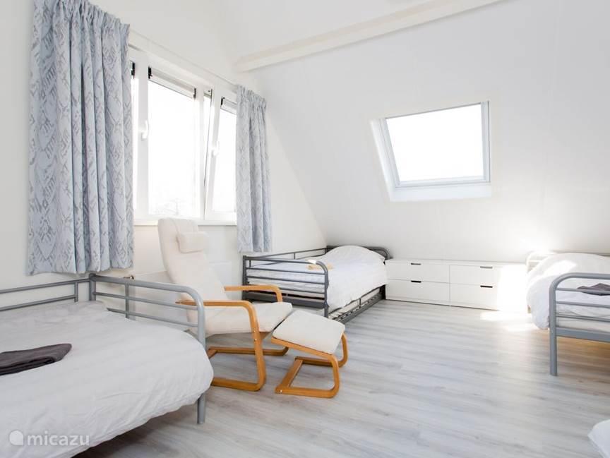 Slaapkamer 2 op de eerste verdieping met vier éénpersoonsbedden.