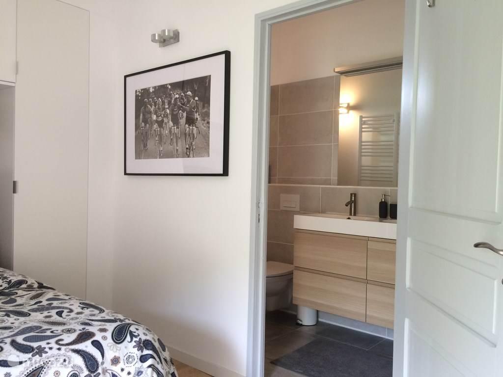 Luxe badkamer met douche, toilet en dubbele wastafel, toegang vanuit slaapkamer