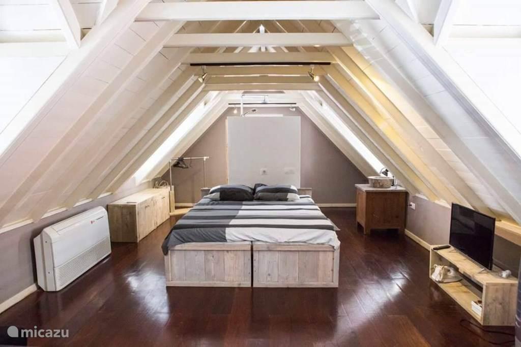 Het bed met achter de wand douche & toilet