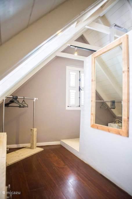 Grote spiegel, rek om kleding op te hangen en kledingkast.