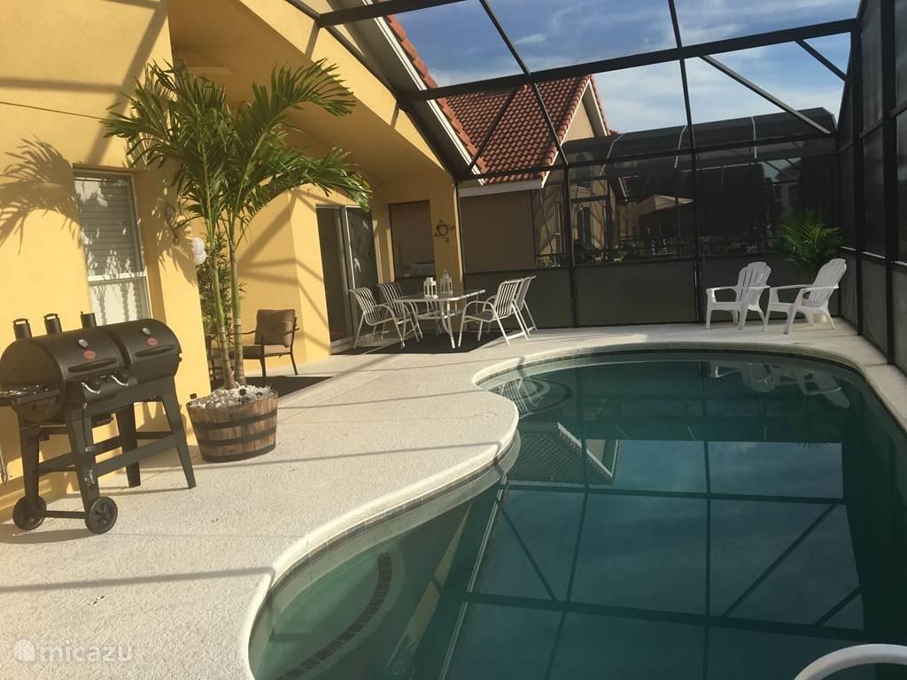 Modern ingericht zwembad met veranda.