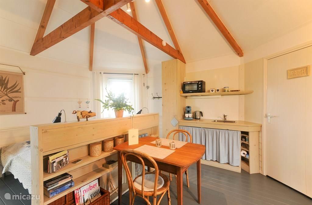 In de achthoekige ruimte vind je een ruim tweepersoonsbed en eenvoudige kitchenette, met oventje en elektrisch kookplaatje (één pits) en heb je een mooi uitzicht over de weilanden.