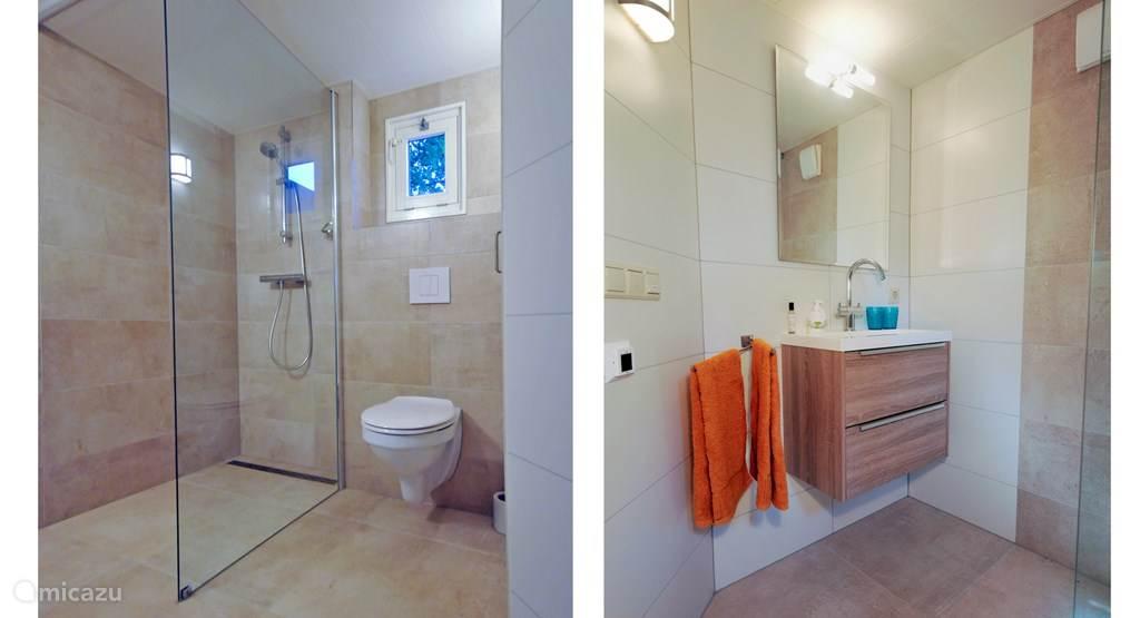 De royale badkamer heeft een inloopdouche, wastafel en toilet