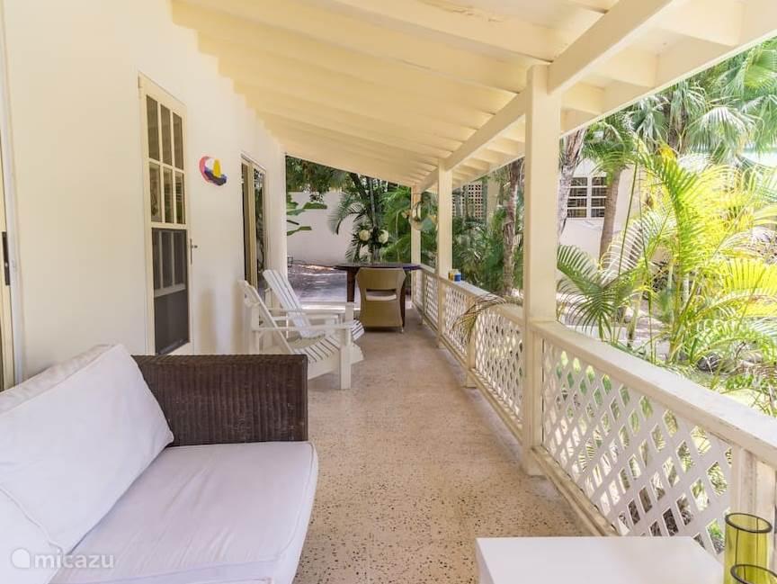 Porch bij vakantiewoning met comfortabele bank, nog comfortabelere adirondack stoelen en eettafel