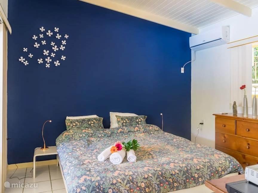Slaapkamer met ruim tweepersoonsbed (180 x 210cm), TV, Airco, ladekast en ruime kledingkast, raam met hor en schuifdeuren naar de porch