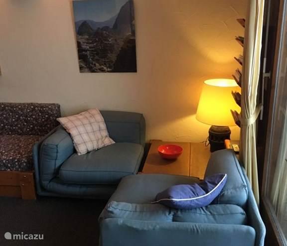 Lekkere fauteuils bij het raam en deur naar het terras en de tuin.
