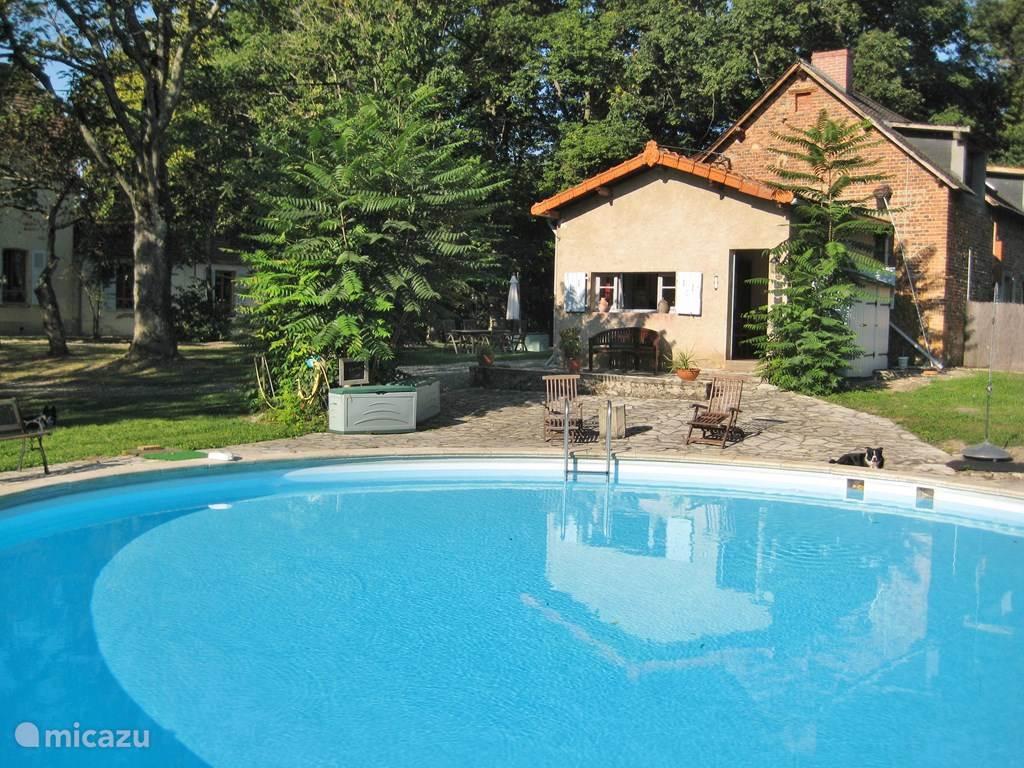 Het zwembad (rond met een diameter van 10 mtr) met daarachter het oude koetshuis waarin de gites zijn gesitueerd.