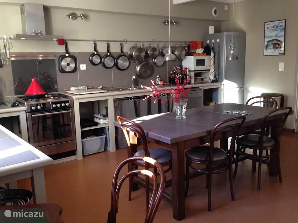 De ruime keuken / eetkamer met semiprofessioneel keukengerei.