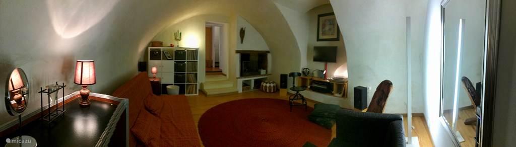 De woonkamer, alias slaapkamer 1, met TV, stereo, platenspeler, comfortabele slaapbank en open haard.