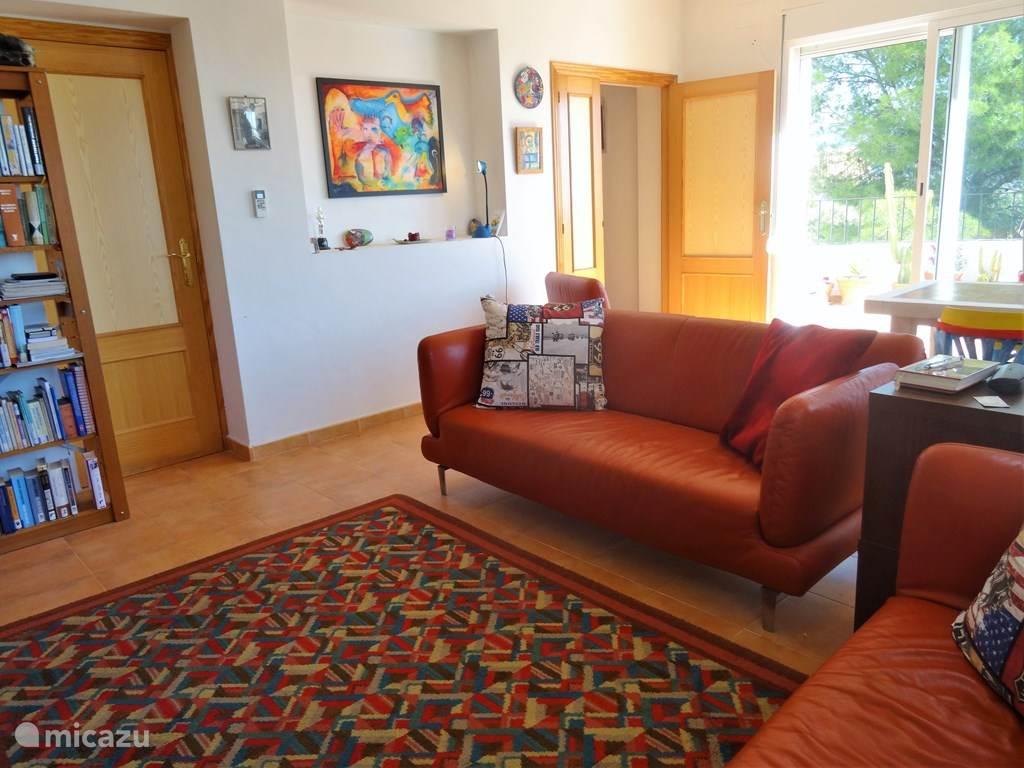 Lichte gezellige woonkamer met openslaande deuren naar terras