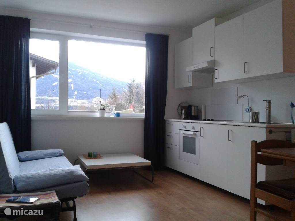 Living area and kitchen with views of garden and mountains
