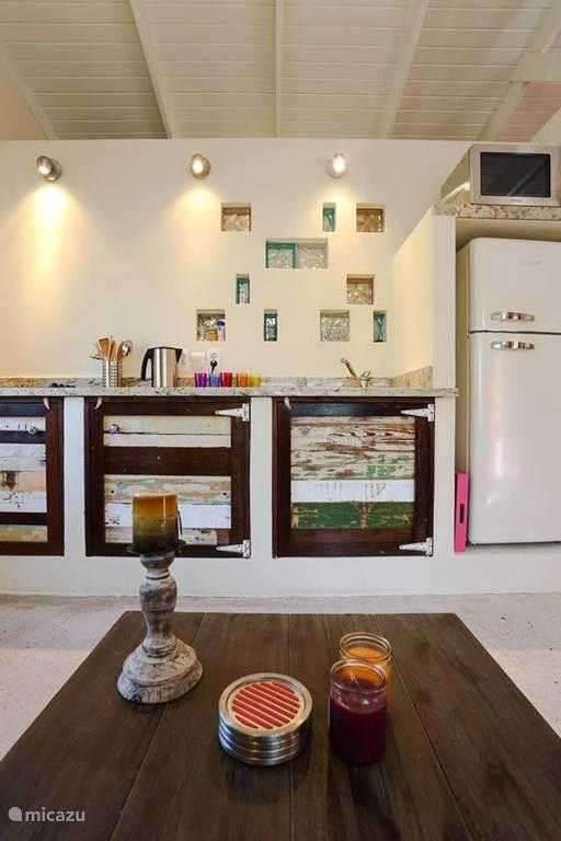 Keuken met ijskast, combi-oven en electrische kookplaat.