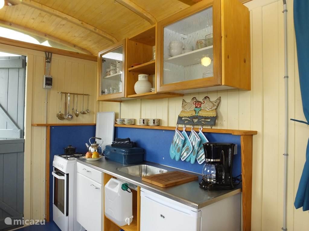 Uitgebreide keuken met gasfornuis, oven, koelkast en compleet voorzien van serviesgoed.