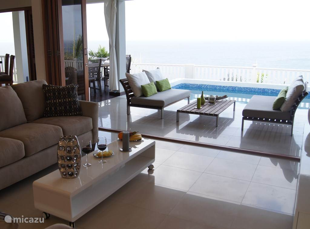 Spacious living room on the ground floor of the villa, with the adjoining terrace and swimming pool.