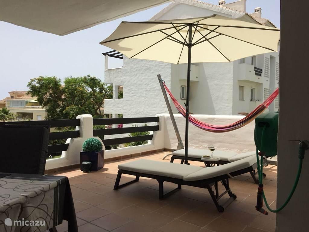 Het zonnige terras met ligstoelen en parasol