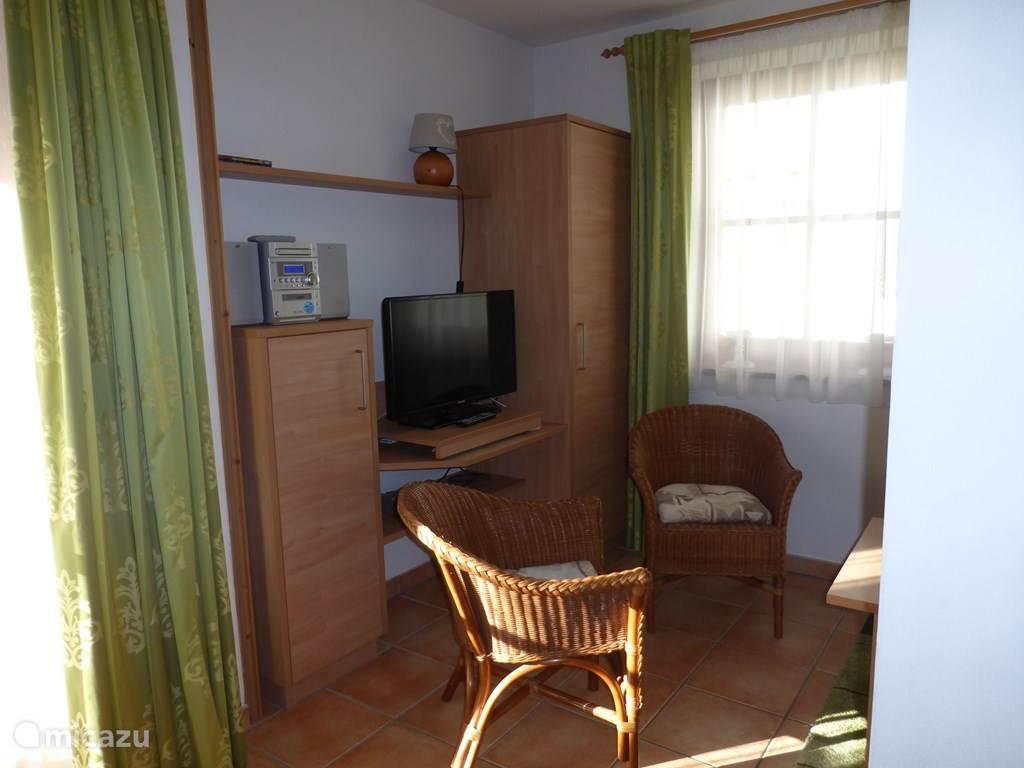 Vertrek met twee stoelen, tweepersoonsslaapbank en tv. Het vertrek is d.m.v. een houten schuifpui te scheiden van de eetkamer/hoek om zo een extra tweepersoons slaapkamer te creëren