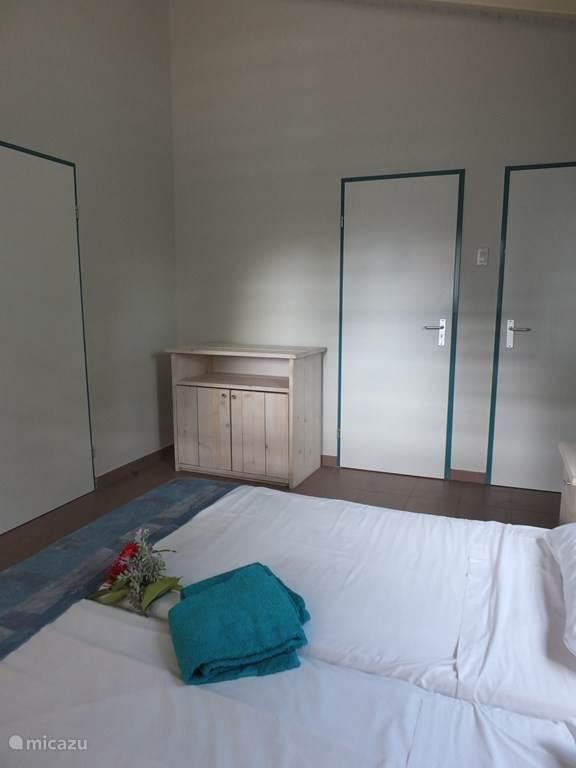 slaapkamer appartement met kastdeur en deur naar badkamer