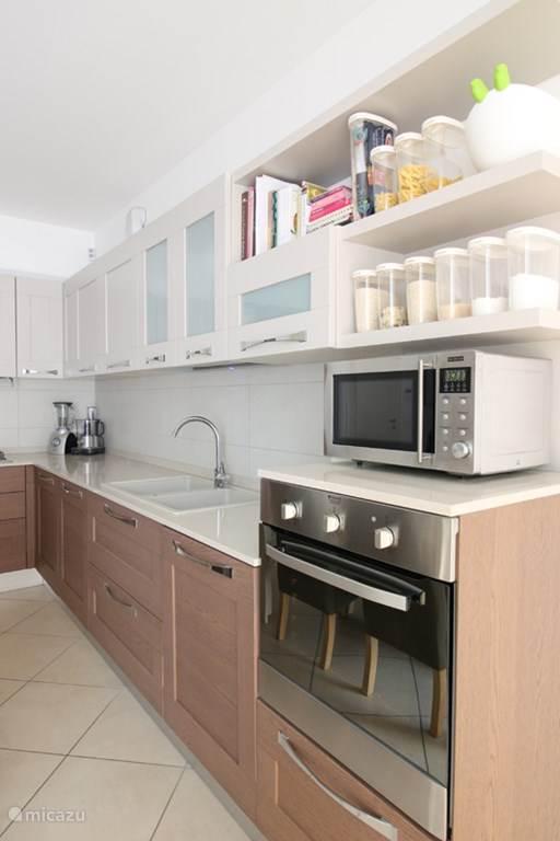 De keuken met oa oven, magnetron en vaatwasser.
