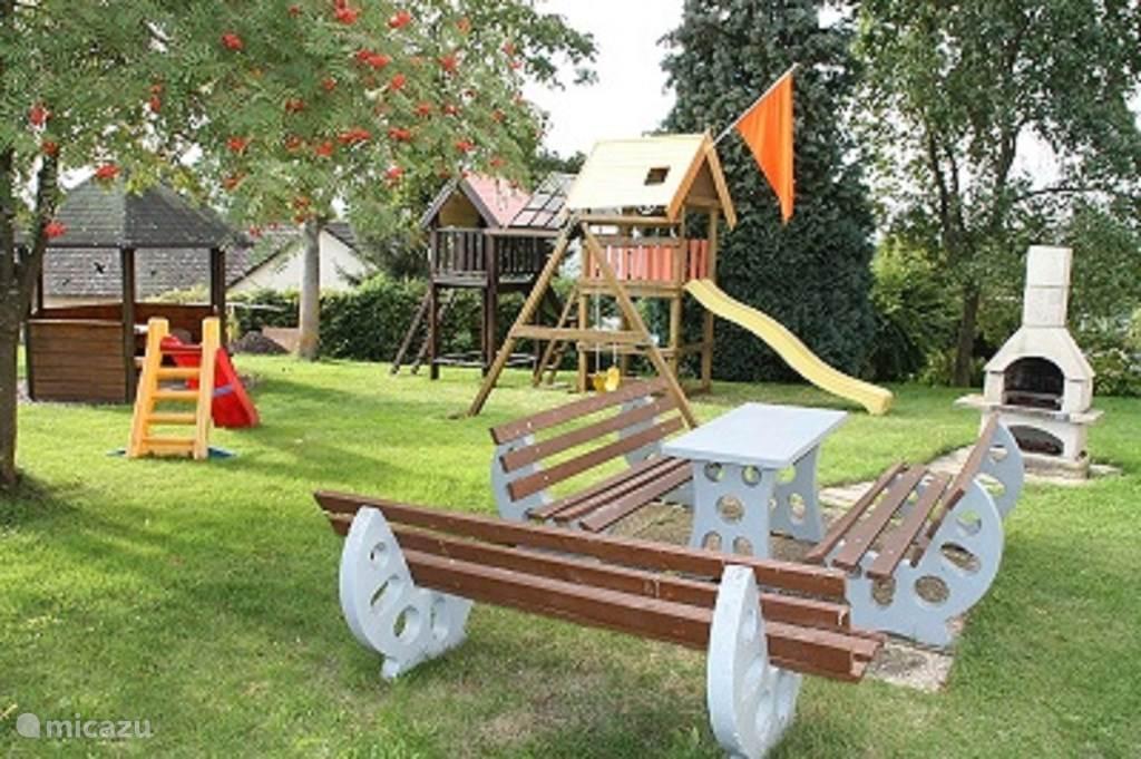 Tuin met barbeque en speeltoestellen