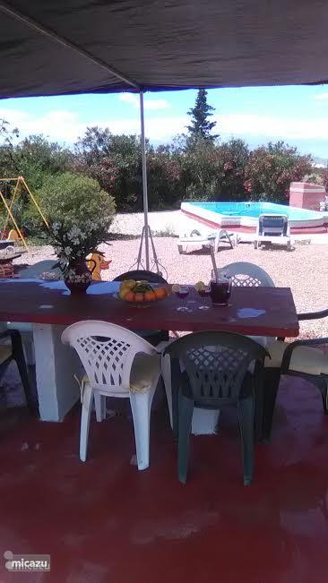 Overkapt terras met grote tafel met uitzicht op het zwembad. Zwembad is in gebruik van april-oktober, evt. verlenging tot november.