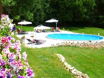 Zwembad met ligstoelen en parasols