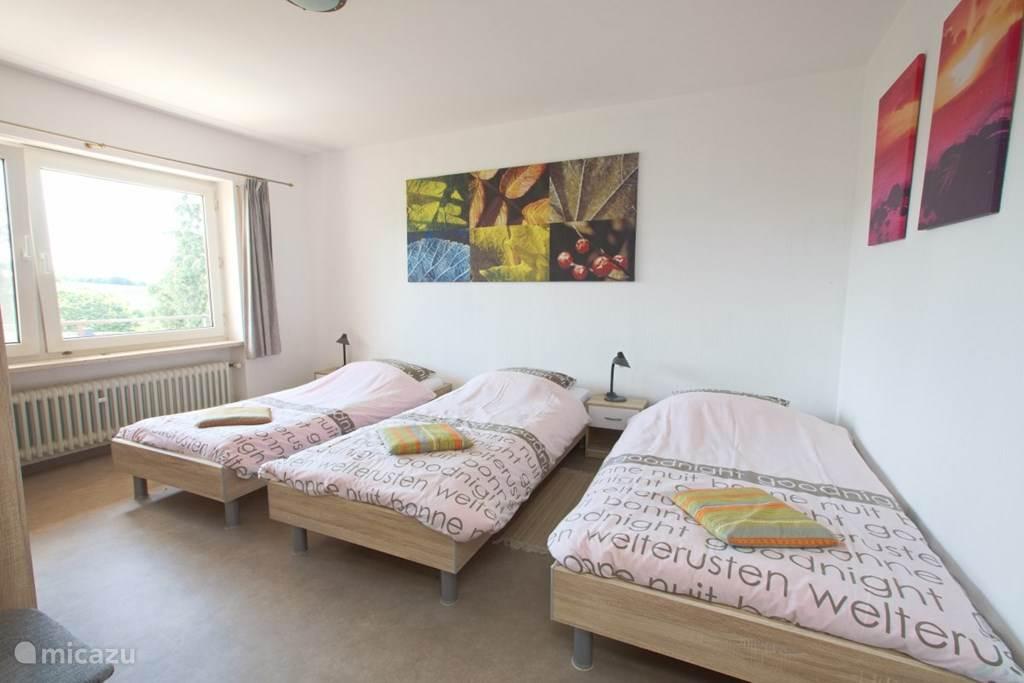 Slaapkamer met 3 een-persoonsbedden