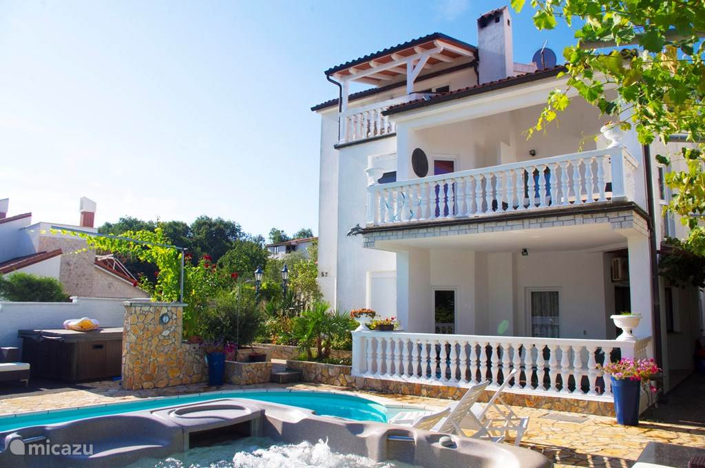 The villa with the three apartments on each floor with the Jacuzzi and the swimming pool in the foreground