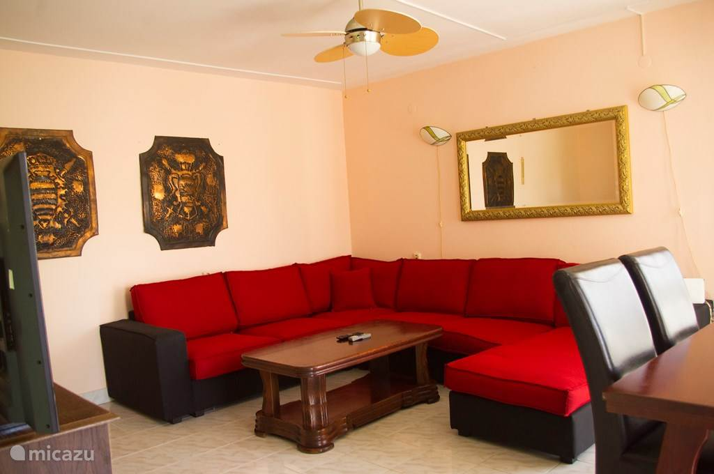 The spacious living room of apartment A with the corner sofa and the 55 inch smart TV