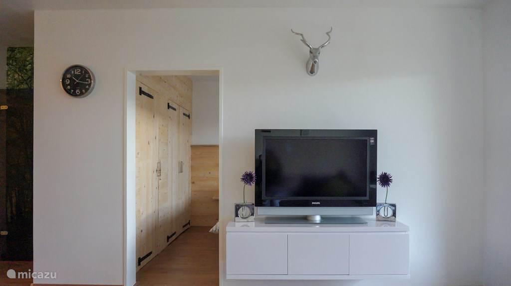Woonkamer met flatscreen tv voorzien van het Nederlandse + Duitse zenderpakket en een WII spelcomputer