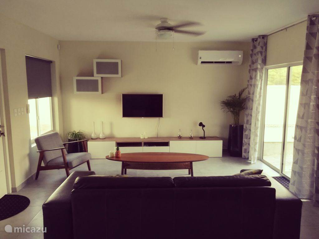 Wohnzimmer mit Dreiersofa, Fauteuille und Fernseher mit Netflix