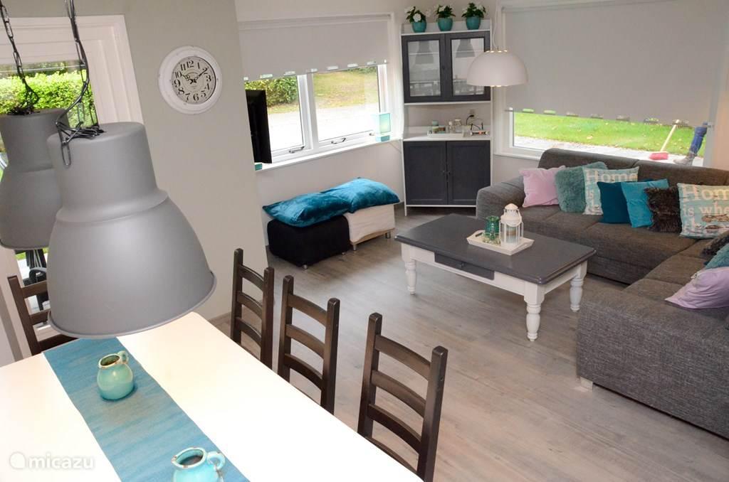 Een mooie ingerichte kamer met een grote tv met mooie blauw/groene tinten. Op de bank heel sfeervol allerlei kussentjes.