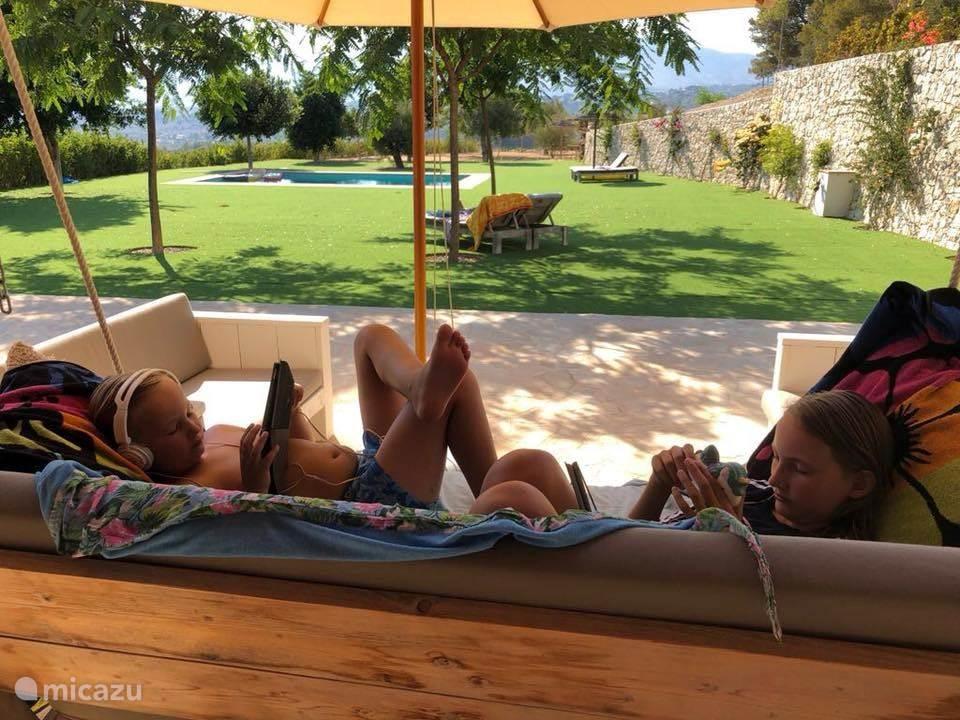 Loungen op de veranda met uitzicht op de tuin en zwembad