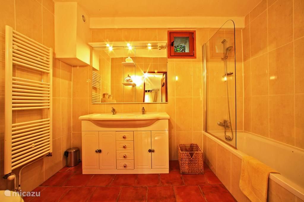 Badkamer met bad, wastafel en toilet.