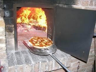 Pizza's worden gebakken in een orrigineel houtgestookte pizza-oven