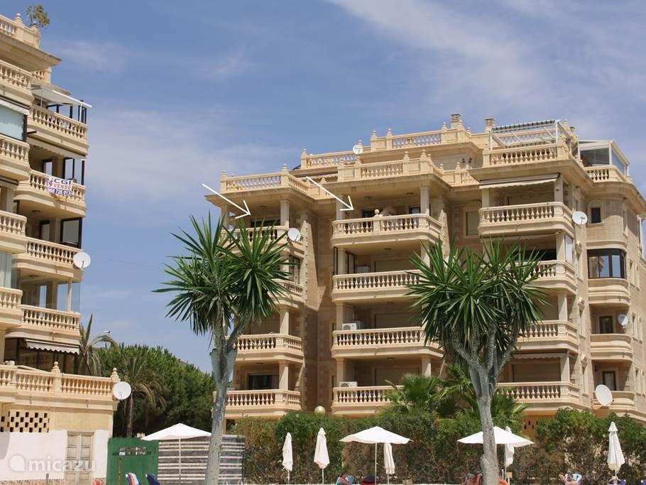 facade van ons apartementsgebouw, pijl links terras woonkamer, pijl rechts terras keuken.