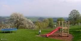 tuin met kinderspeeltoestellen: schommel, glijbaan, zandbak, trampoline.