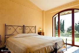 Comfortabele  lichte slaapkamer nr. 1 met airco en met terracotta vloer. Romantische smeedijzeren bedden met een uitstekende matras 200x200 cm. Heerlijk uitzicht over de tuin en de Toscaanse heuvels. Openslaande deur. Horren aanwezig.
