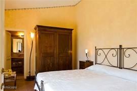 Slaapkamer nr. 2 met airco en terracotta vloer. Originele Toscaanse kleuren en smeedijzeren bedden. Heelijk matras 200x200 cm. Met doorzicht naar de eigen  marmeren badkamer nr. 2 met douche, toilet en bidet