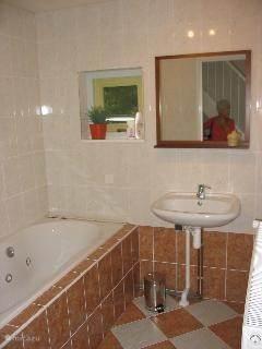 badkamer met whirlpool en aparte douche.