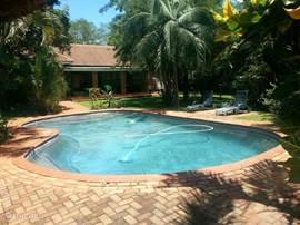 zwembad met deel van de achterkant van het huis.